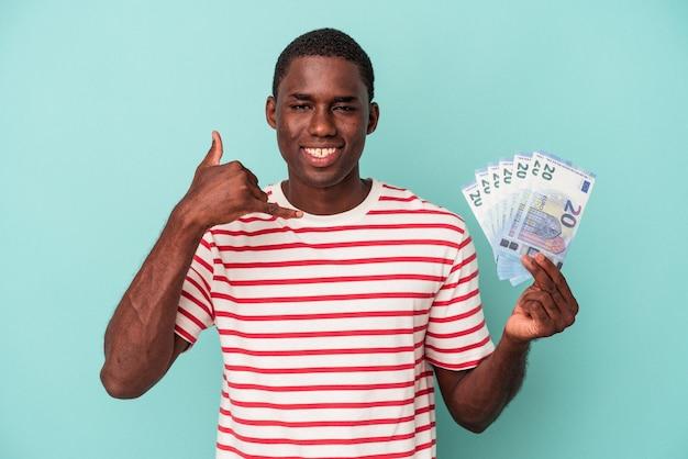 指で携帯電話の呼び出しジェスチャーを示す青い背景に分離された紙幣を保持している若いアフリカ系アメリカ人の男。