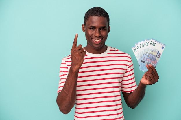 파란색 배경에 격리된 지폐를 들고 있는 젊은 아프리카계 미국인 남자는 손가락으로 1번을 보여줍니다.