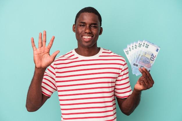 파란색 배경에 격리된 지폐를 들고 있는 젊은 아프리카계 미국인 남자는 손가락으로 5번을 보여주며 밝게 웃고 있습니다.