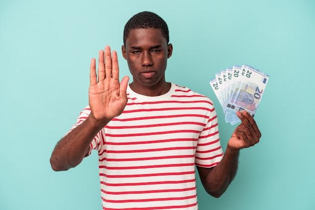 青の背景に分離された紙幣を持っている若いアフリカ系アメリカ人の男は、一時停止の標識を示す伸ばした手で立って、あなたを防ぎます。