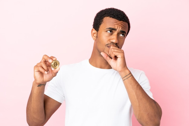 孤立したピンクの背景の上にビットコインを保持し、見上げる若いアフリカ系アメリカ人の男