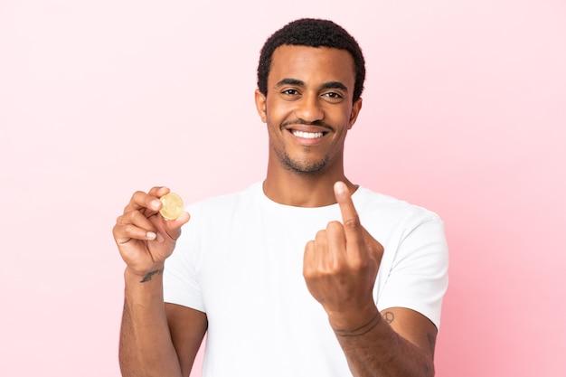 来るジェスチャーをしている孤立したピンクの背景の上にビットコインを保持している若いアフリカ系アメリカ人の男