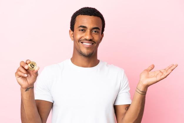孤立したピンクの背景の上にビットコインを保持している若いアフリカ系アメリカ人の男