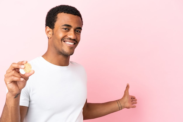 孤立したピンクの背景の上にビットコインを持って、来るように誘うために手を横に伸ばしている若いアフリカ系アメリカ人の男