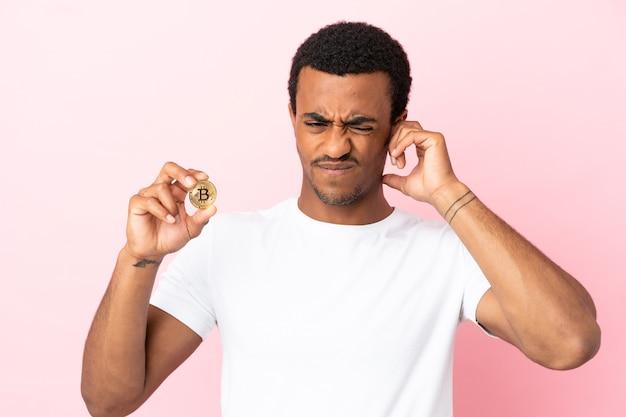 Молодой афроамериканец, держащий биткойн на розовом фоне, разочарован и закрывает уши