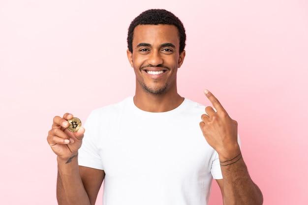 親指を立てるジェスチャーを与える孤立したピンクの背景の上にビットコインを保持している若いアフリカ系アメリカ人の男