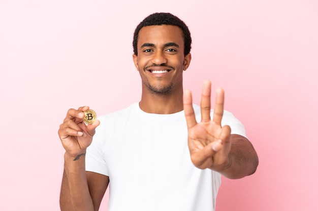 幸せな孤立したピンクの背景の上にビットコインを保持し、指で3を数える若いアフリカ系アメリカ人の男