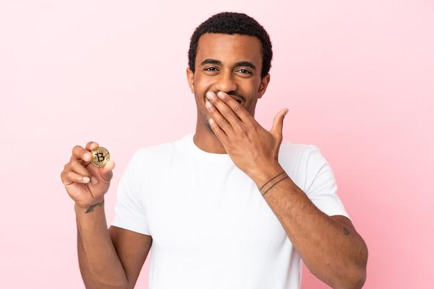 Молодой афроамериканец, держащий биткойн на розовом фоне, счастливый и улыбающийся, прикрывая рот рукой