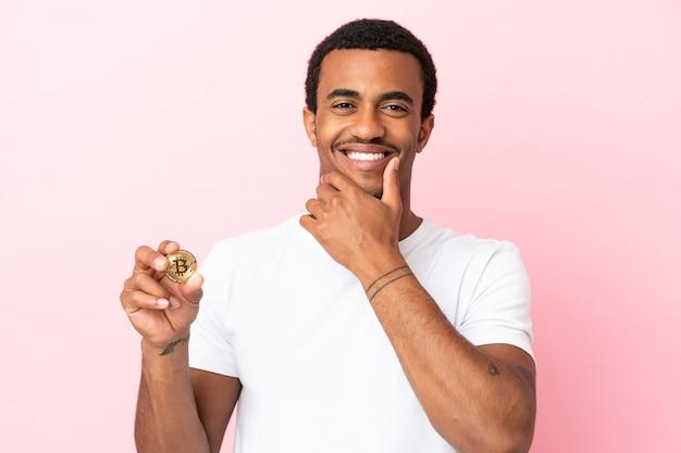幸せと笑顔の孤立したピンクの背景の上にビットコインを保持している若いアフリカ系アメリカ人の男