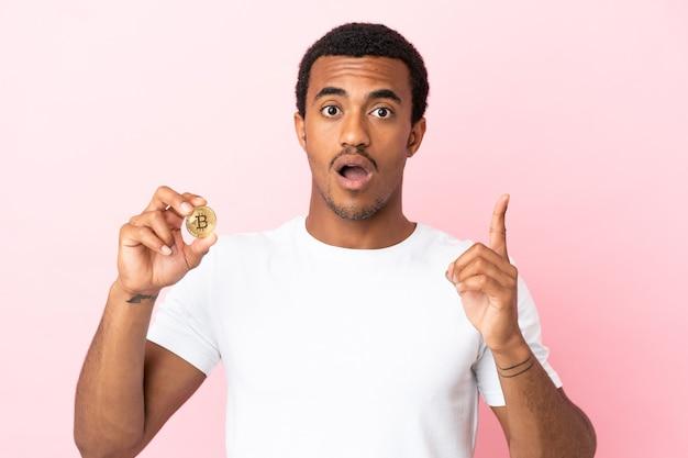 指を持ち上げながら解決策を実現しようとしている孤立したピンクの背景の上にビットコインを保持している若いアフリカ系アメリカ人の男