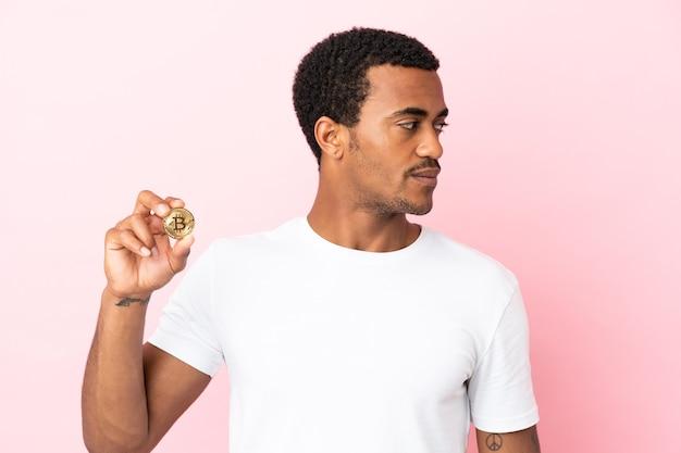 横に見て孤立したピンクの背景の上にビットコインを保持している若いアフリカ系アメリカ人の男