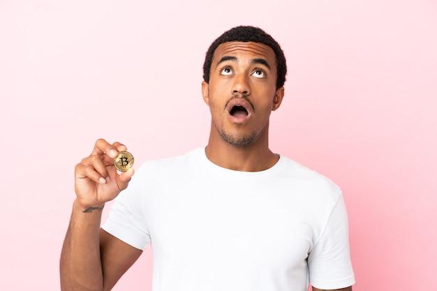 見上げると驚いた表情で孤立したピンクの背景の上にビットコインを保持している若いアフリカ系アメリカ人の男