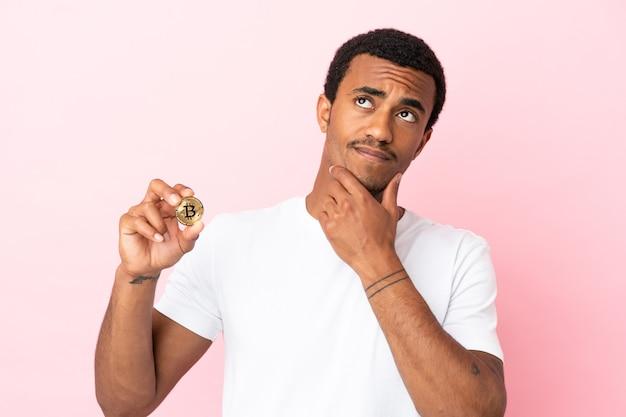 笑顔で見上げる孤立したピンクの背景の上にビットコインを保持している若いアフリカ系アメリカ人の男