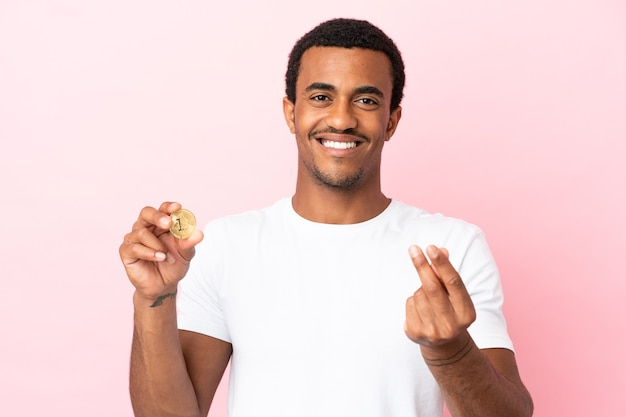 돈 제스처를 만드는 고립 된 분홍색 배경 위에 bitcoin을 들고 젊은 아프리카 계 미국인 남자