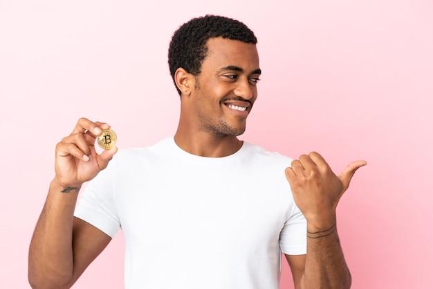 Молодой афроамериканец держит биткойн на изолированном розовом фоне, указывая в сторону, чтобы представить продукт