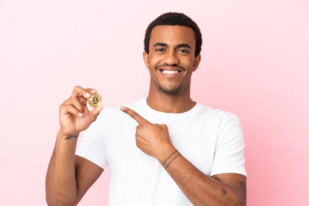 製品を提示する側を指している孤立したピンクの背景の上にビットコインを保持している若いアフリカ系アメリカ人の男
