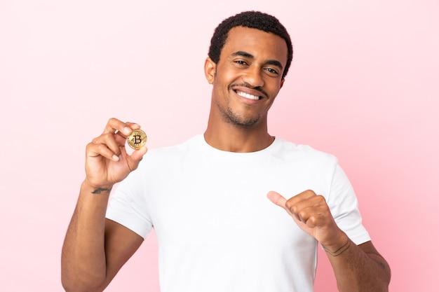 고립된 분홍색 배경 위에 bitcoin을 들고 있는 젊은 아프리카계 미국인 남자