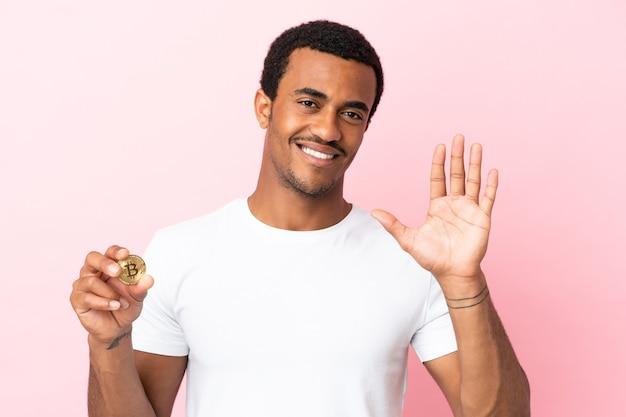 Молодой афроамериканец, держащий биткойн на изолированном розовом фоне, салютует рукой со счастливым выражением лица