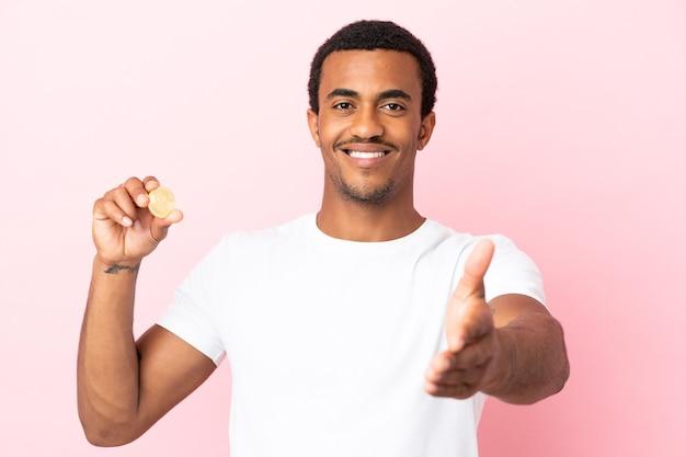 かなりの取引を閉じるために握手する孤立したピンクの背景の上にビットコインを保持している若いアフリカ系アメリカ人の男
