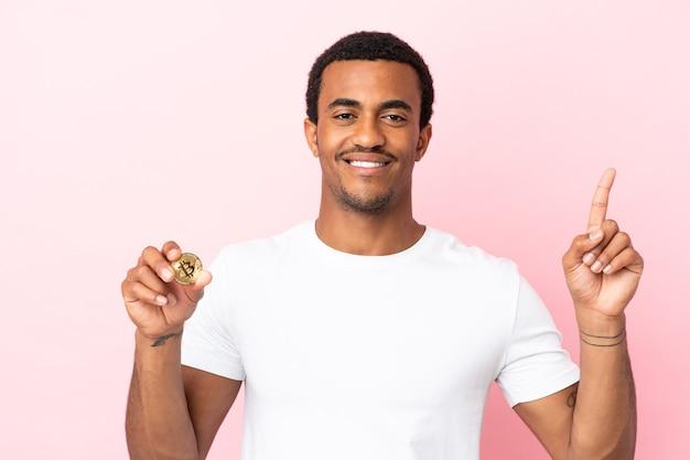 孤立したピンクの背景の上にビットコインを保持し、最高の兆候を示して指を持ち上げる若いアフリカ系アメリカ人の男