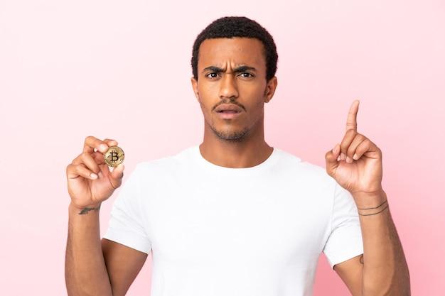 指を上に向けるアイデアを考えて孤立したピンクの背景の上にビットコインを保持している若いアフリカ系アメリカ人の男