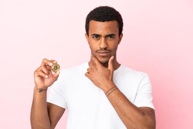 孤立したピンクの背景思考の上にビットコインを保持している若いアフリカ系アメリカ人の男