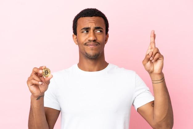 指が交差し、最高を願って孤立したピンクの背景の上にビットコインを保持している若いアフリカ系アメリカ人の男
