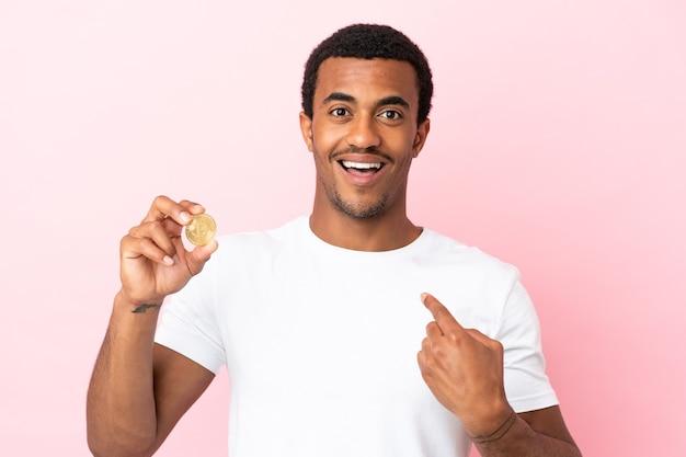 놀란 표정으로 고립된 분홍색 배경 위에 bitcoin을 들고 있는 젊은 아프리카계 미국인 남자