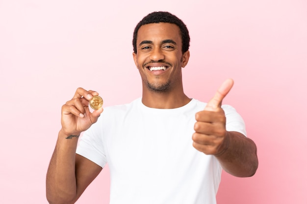 何か良いことが起こったので、親指を立てて孤立したピンクの背景の上にビットコインを保持している若いアフリカ系アメリカ人の男
