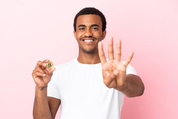 Молодой афроамериканец, держащий биткойн над изолированной розовой поверхностью, счастлив и считает четыре пальцами