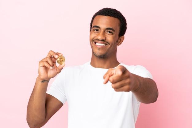 Молодой афроамериканец держит биткойн над изолированной розовой поверхностью, указывая вперед со счастливым выражением лица