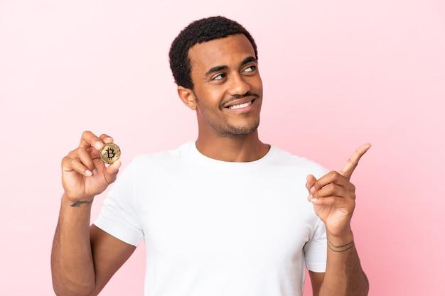 Молодой афроамериканец держит биткойн над изолированной розовой поверхностью, указывая на отличную идею