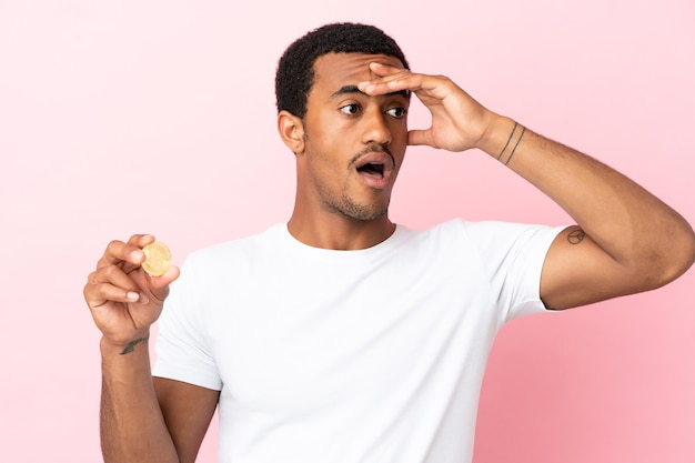 측면을 보면서 깜짝 제스처를 하 고 고립 된 분홍색 벽 위에 bitcoin을 들고 젊은 아프리카 계 미국인 남자