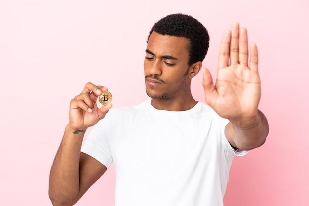 Молодой афроамериканец держит биткойн над изолированной розовой стеной, делая жест стоп и разочарованный