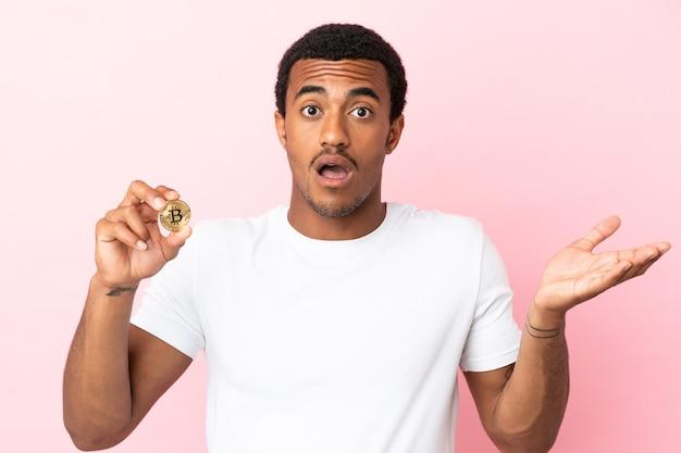 충격 된 표정으로 고립 된 분홍색 벽 위에 bitcoin을 들고 젊은 아프리카 계 미국인 남자