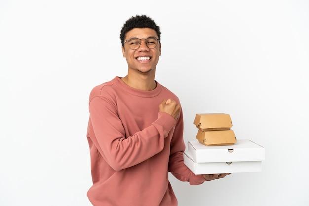 Молодой афроамериканец, держащий гамбургер и пиццу на белом фоне, празднует победу