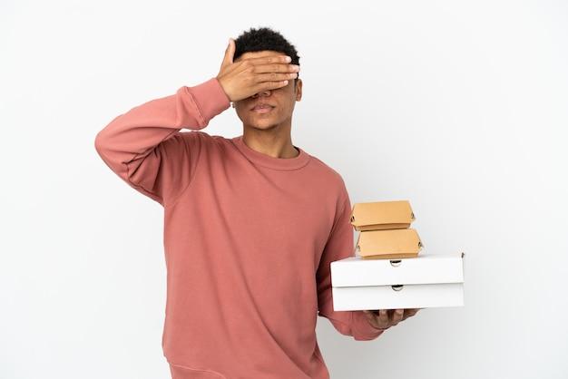 Молодой афро-американский мужчина, держащий гамбургер и пиццу, изолированные на белом фоне, закрывая глаза руками. не хочу что-то видеть