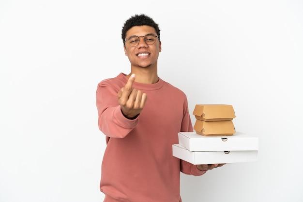 Молодой афроамериканец, держащий гамбургер и пиццу, изолированные на белом фоне, делает приближающийся жест