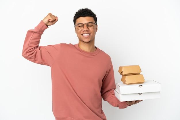 Молодой афроамериканец, держащий гамбургер и пиццу на белом фоне, делает сильный жест