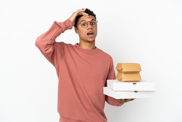 Молодой афроамериканец, держащий гамбургер и пиццу на белом фоне, делает неожиданный жест, глядя в сторону