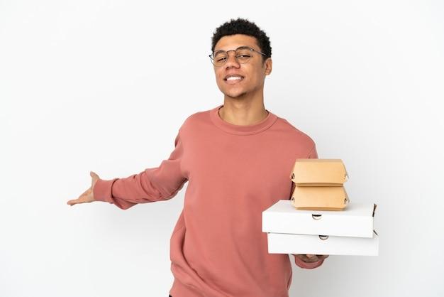 来るように誘うために手を横に伸ばして白い背景で隔離のハンバーガーとピザを保持している若いアフリカ系アメリカ人の男