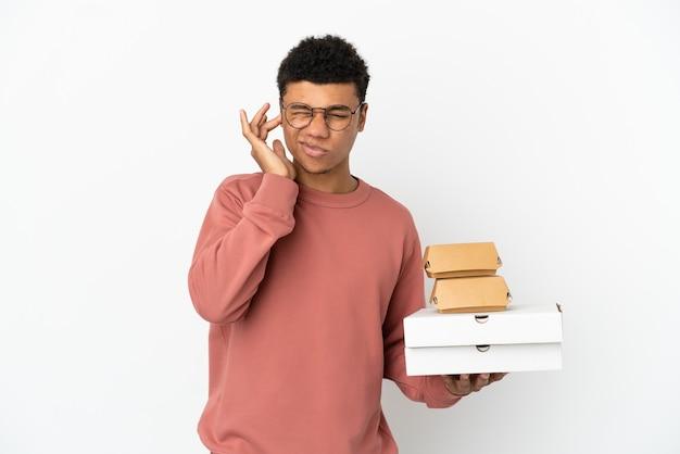 Молодой афроамериканец, держащий гамбургер и пиццу на белом фоне, разочарован и закрывает уши