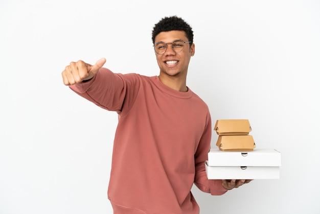 親指を立てるジェスチャーを与える白い背景で隔離のハンバーガーとピザを保持している若いアフリカ系アメリカ人の男