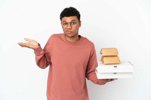Молодой афроамериканец, держащий гамбургер и пиццу на белом фоне, сомневаясь, поднимая руки