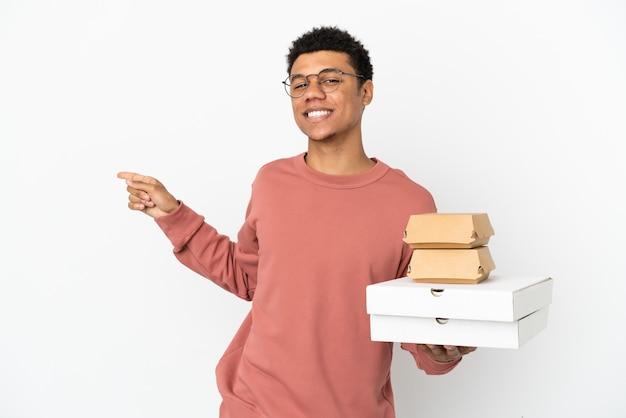 Молодой афроамериканец, держащий гамбургер и пиццу на белом фоне, указывая пальцем в сторону