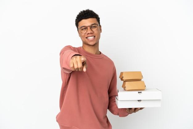 Молодой афроамериканец, держащий гамбургер и пиццу, изолированные на белом фоне, указывая спереди с счастливым выражением лица