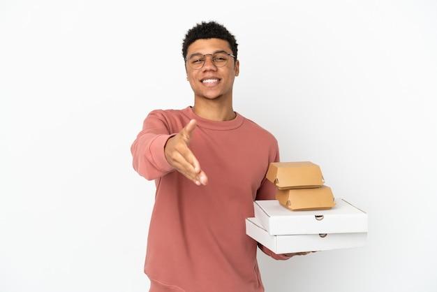 Молодой афроамериканец, держащий гамбургер и пиццу на белом фоне, пожимая руку для заключения хорошей сделки
