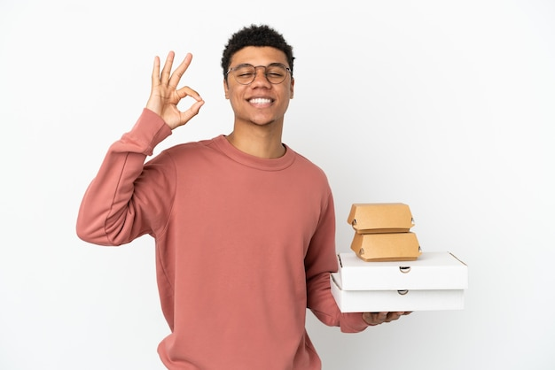 Молодой афроамериканец, держащий гамбургер и пиццу, изолированные на белом фоне, показывает пальцами знак ок
