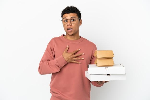 Молодой афроамериканец, держащий гамбургер и пиццу на белом фоне, удивлен и шокирован, глядя вправо