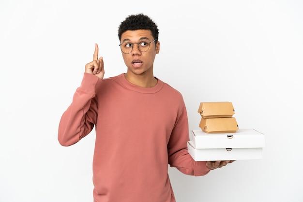 Молодой афроамериканец, держащий гамбургер и пиццу, изолированные на белом фоне, думает о идее, указывая пальцем вверх